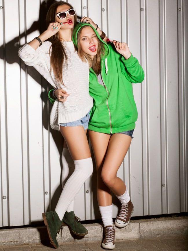 Портрет двух молодых симпатичных девушек сосать леденцы на палочке, на откр